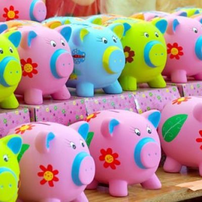 Many porcelais colorful money pigs for sale on a stand