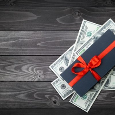 Black matte gift box with a bow with dollars banknotes on a dark wooden backgroung. top view