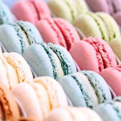 Box of fresh colorful macarons. Extreme shallow depth of field with selective focus on center blue macaron.